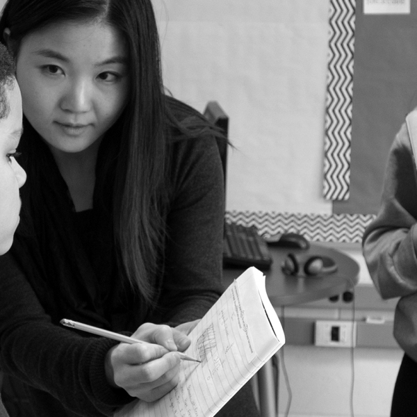Asian instructor with notebook and pencil in hand, showing a boy his work, a girl is standing to the right, also with a notebook in hand, waiting for instructor to check her work