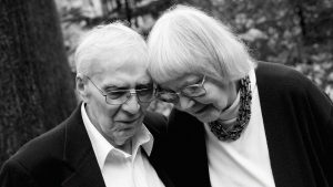 Elder Peter and Liz with glasses on tilting their heads toward each other looking downward