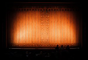 A view of a theatre stage in a darkened auditorium, with rust-colored curtains lit by spotlights.