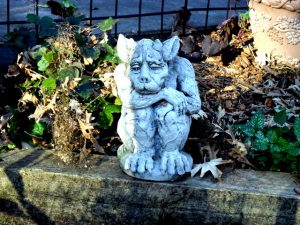 Gargoyle sitting on a stone wall in a garden