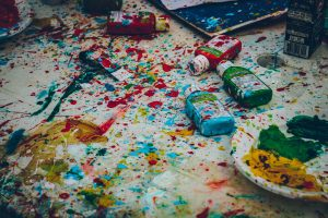 A white canvas covered with paint spatters and squeeze bottles of paint.